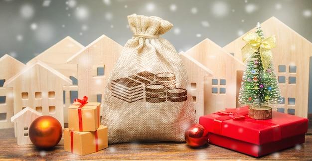 돈 가방, 목조 주택, 크리스마스 트리 및 선물. 프리미엄 사진