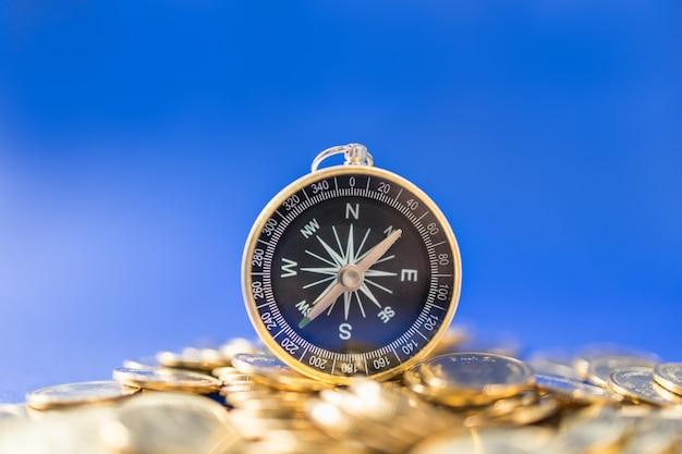 お金、ビジネス、方向および計画のコンセプト。コピースペースを持つ青の金貨の山にコンパスのクローズアップ。 Premium写真