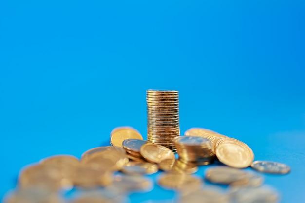 お金、ビジネス、リスクの概念。スタックとコピースペースと青に金貨の山のクローズアップ。 Premium写真