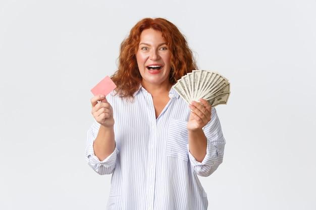 Concetto di denaro, finanza e persone. donna rossa di mezza età allegra ed eccitata in camicetta casual, in possesso di denaro e carta di credito con un sorriso ottimista, in piedi su sfondo bianco. Foto Gratuite