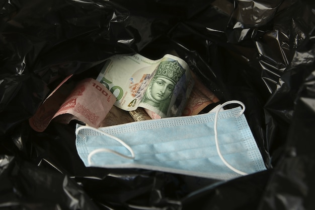 Money from around the world and a face mask inside a black plastic trash bag. Free Photo