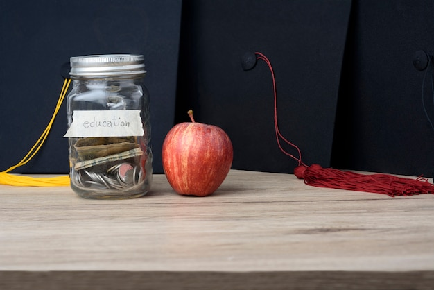 Money in a glass jar put on the table for university study. Premium Photo