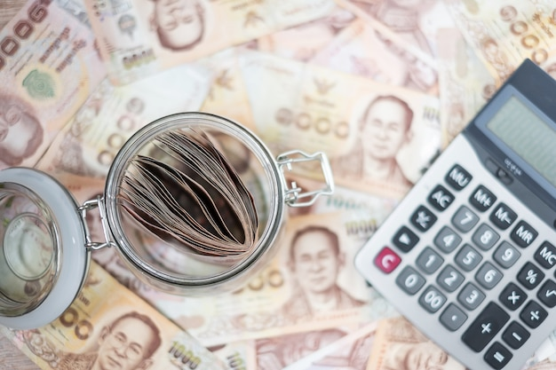 Money glass jar with calculator. business, investment, retirement planning, finance Premium Photo