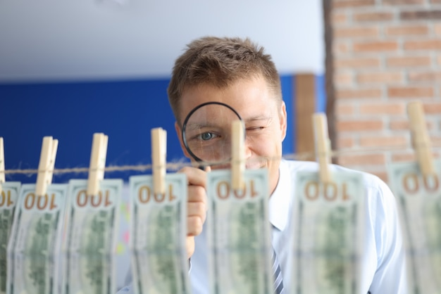 Money laundering. man looks through magnifying glass at one hundred dollar bills hanging on clothespins. Premium Photo