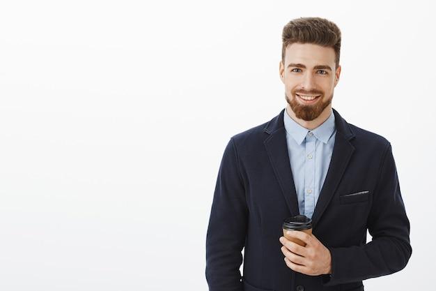 Деньги любят уверенность. уверенный в себе харизматичный и умный красавец с каштановыми волосами, бородой и голубыми глазами держит бумажный стаканчик кофе, счастливо улыбаясь, встречая симпатичную девушку после работы в кафе Бесплатные Фотографии