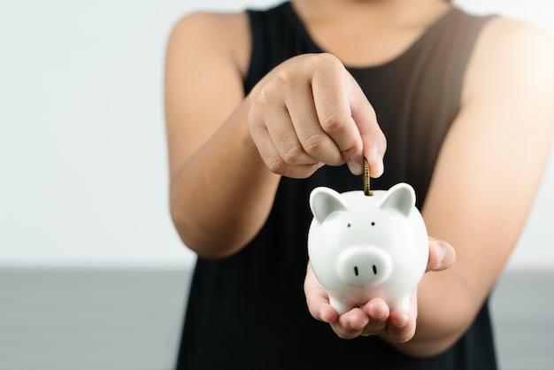 Money saving and donation concept, child put money on cute white piggy bank Premium Photo