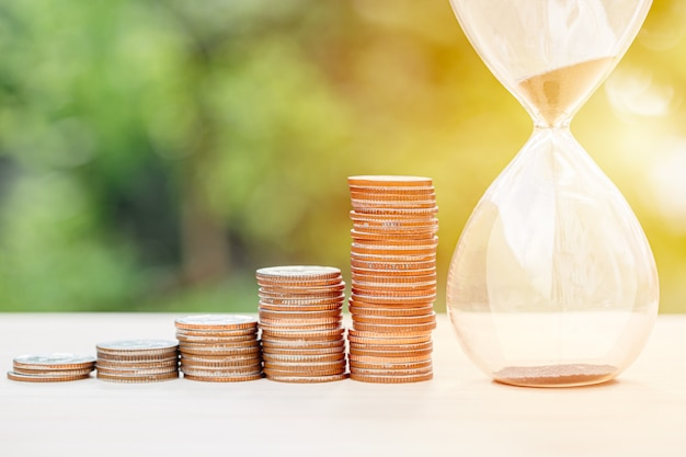 Money times memory concept, coins stack with sand hourglass Premium Photo