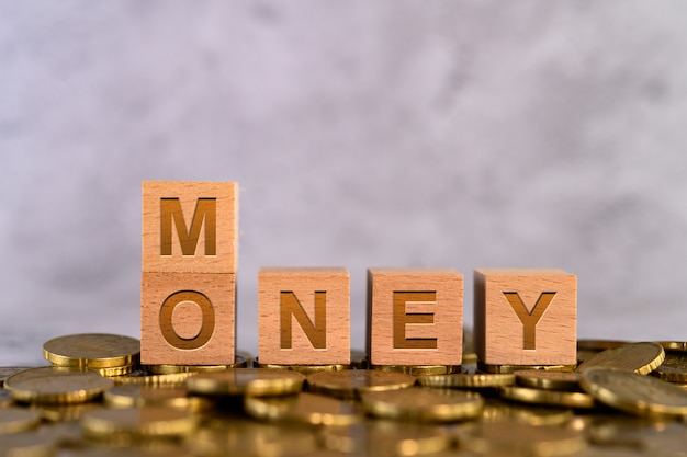 Money word alphabet wooden cube letters placed on a gold coin Free Photo