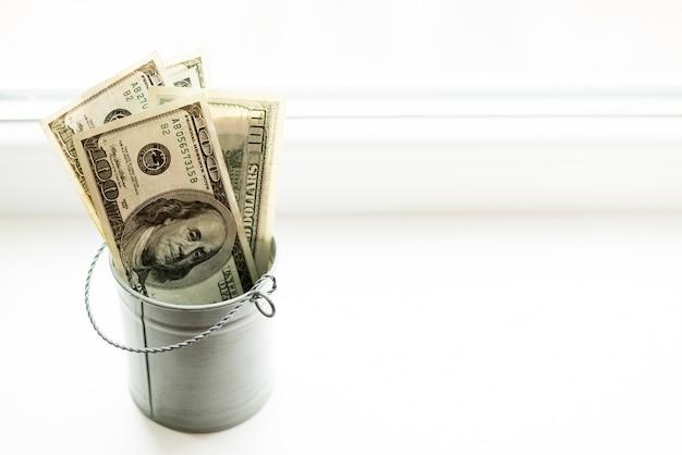 Moneybox, dollars in bucket on white window.light background Premium Photo