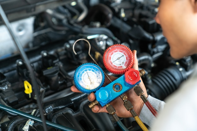 Monitor tool on car engine ready to check and fixed car air conditioner system in car garage Premium Photo