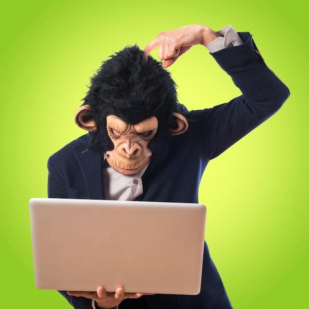 Человек-обезьяна сомневается в своем ноутбуке на цветном фоне Premium Фотографии
