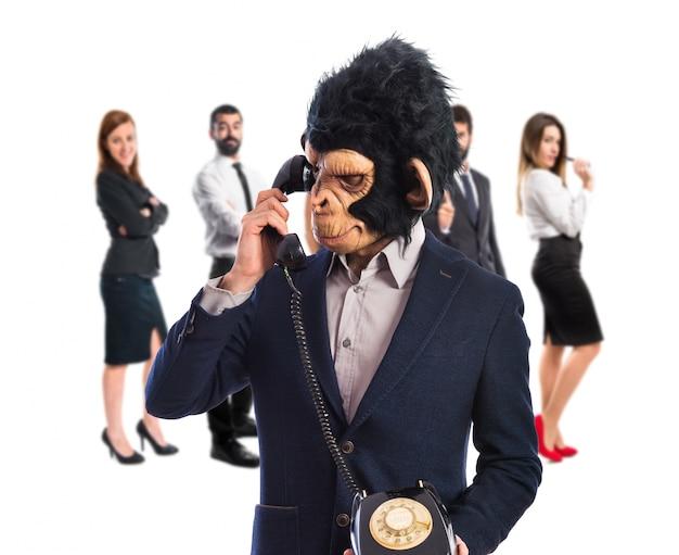 Человек-обезьяна разговаривает со старинным телефоном Premium Фотографии