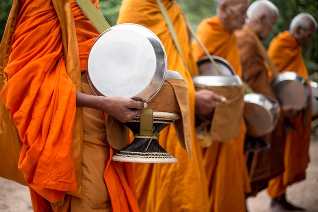 Monks alms round or receive food offerings moment. Premium Photo