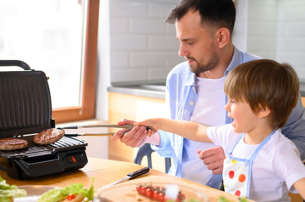 Отец с одним родителем и ребенок готовят гамбургеры Бесплатные Фотографии