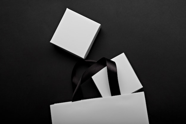 Monochrome photo of a white paper bag and boxes on a black background. place for your logo branding Premium Photo
