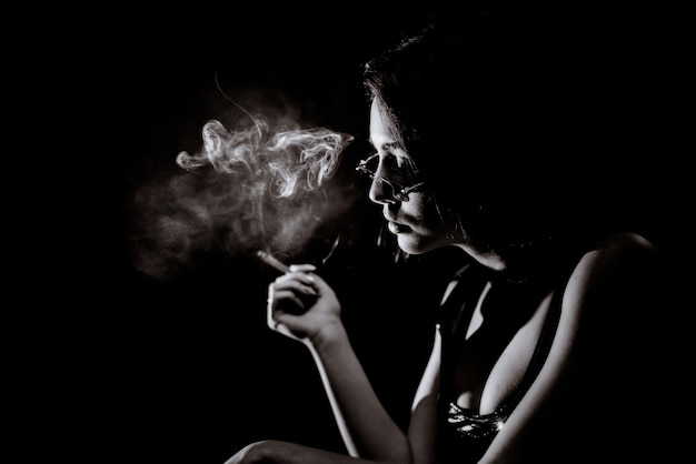 Monochrome portrait of young girl who is smoking  with big decollete and in eyeglasses Free Photo