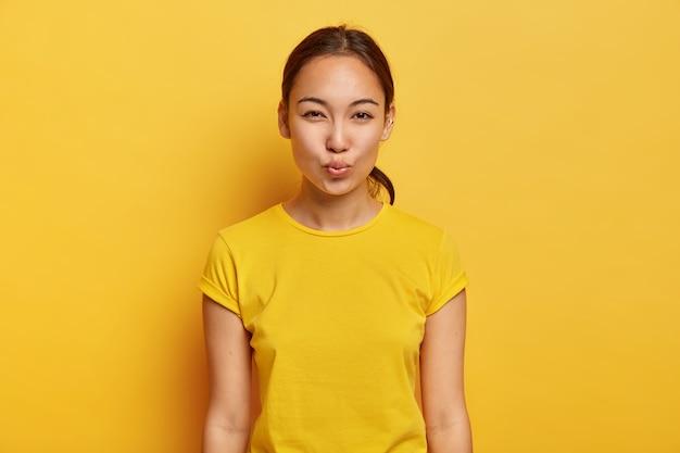 아시아 외모, 건강한 피부, 귀에 피어싱을 가진 아름다운 여성의 흑백 샷은 입술을 접고 키스를 기다립니다. 얼굴 표정 개념 무료 사진