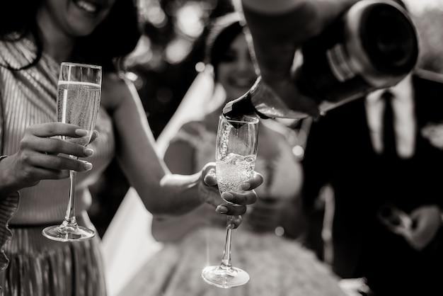 Монохромный вид разлива бутылки в бокалы и бокалы для шампанского в нежных женских руках Бесплатные Фотографии