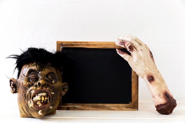 Monster hand and mask near blackboard Free Photo
