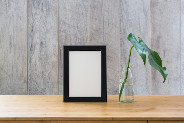 Monstera leaf in glass bottle and photo frame on wooden table Free Photo
