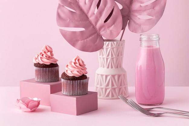 モンステラ植物とピンクのカップケーキの配置 無料写真