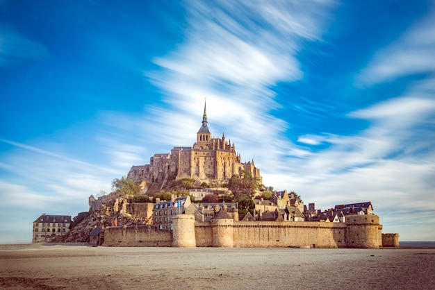 Mont saint michel and its abbey with the sea at low tide and clouds moving by the strong wind Premium Photo