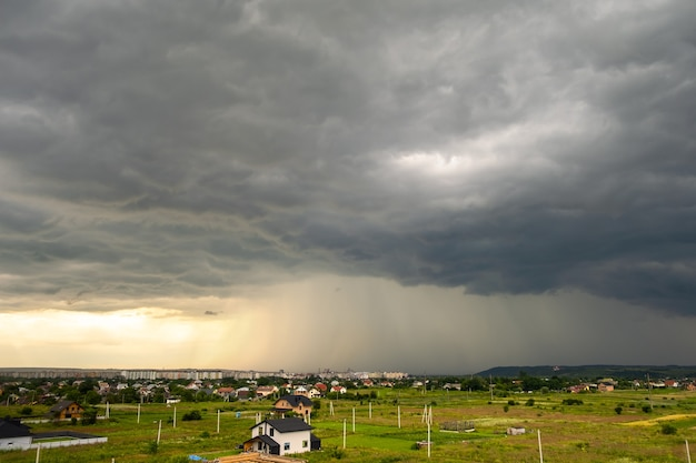 Moody landscape with dark stormy clouds with falling heavy downpour shower rain over distant town buildings in summer. Premium Photo