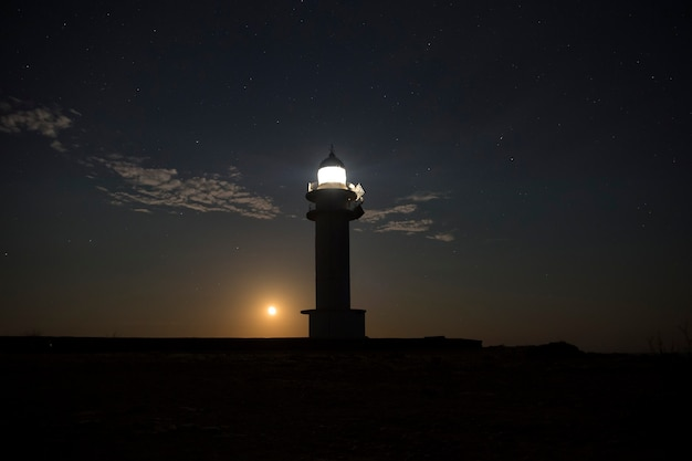 Moon peeks out from behind a lighthouse at night Premium Photo