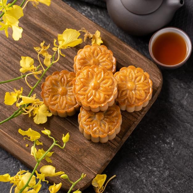 月餅、中秋節の月餅、お茶と黄色い花が付いた黒いスレートテーブルの伝統的なお祭り料理のコンセプトをクローズアップします。 Premium写真