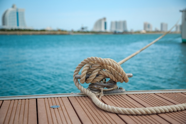 Mooring yacht rope with a knotted end tied around a cleat on a wooden pier Premium Photo