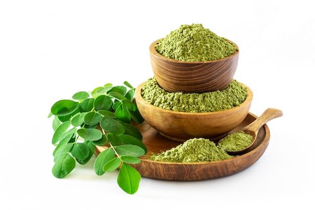 Порошок moringa (moringa oleifera) в деревянном шаре при первоначально свежие листья moringa изолированные на белой предпосылке. Premium Фотографии