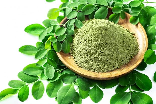 Порошок moringa (moringa oleifera) в деревянном шаре при первоначально свежие листья moringa изолированные на белизне. Premium Фотографии
