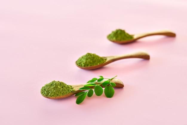 Порошок моринги (moringa oleifera) в деревянных ложках на розовом фоне. Premium Фотографии