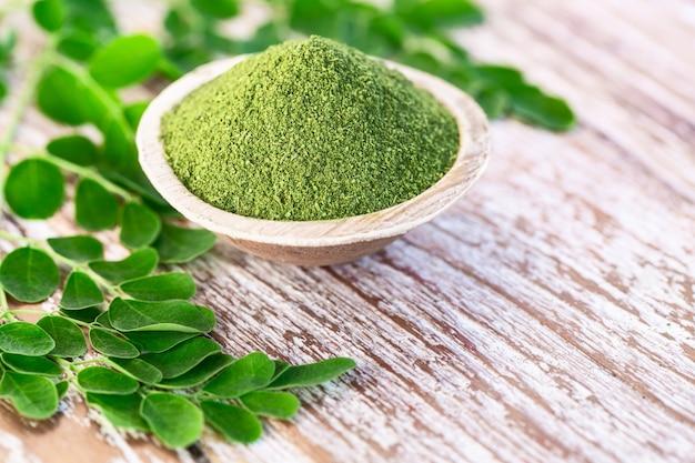 Moringa powder in coconut bowl with original fresh moringa leaves on wooden background Premium Photo