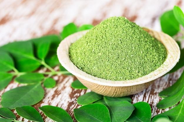 Moringa powder (moringa oleifera) in coconut bowl with original fresh moringa leaves Premium Photo