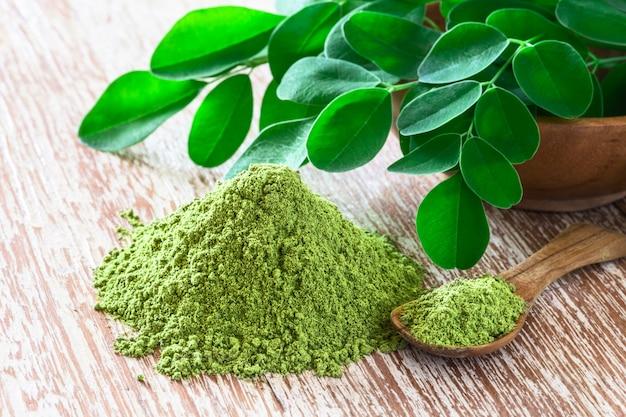 Moringa powder (moringa oleifera) with original fresh moringa leaves on rustic background. Premium Photo