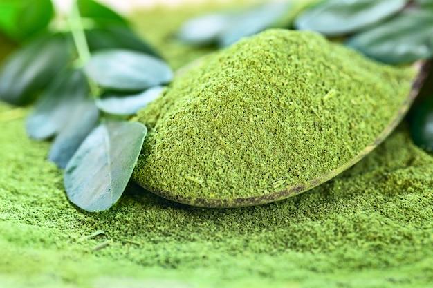 Moringa powder (moringa oleifera) in wooden spoon with original leaves Premium Photo