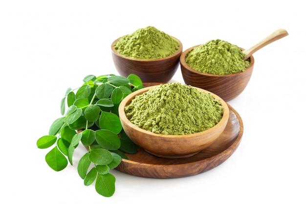 Moringa powder in wooden bowl with original fresh moringa leaves isolated on white background. Premium Photo