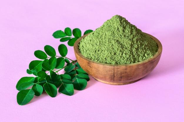 Moringa powder in wooden bowl with original fresh moringa leaves on pink background Premium Photo
