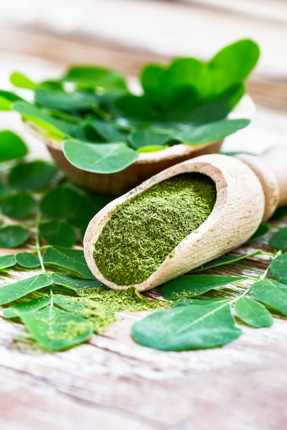 Moringa powder in wooden scoop with original fresh moringa leaves on wooden table close-up. Premium Photo