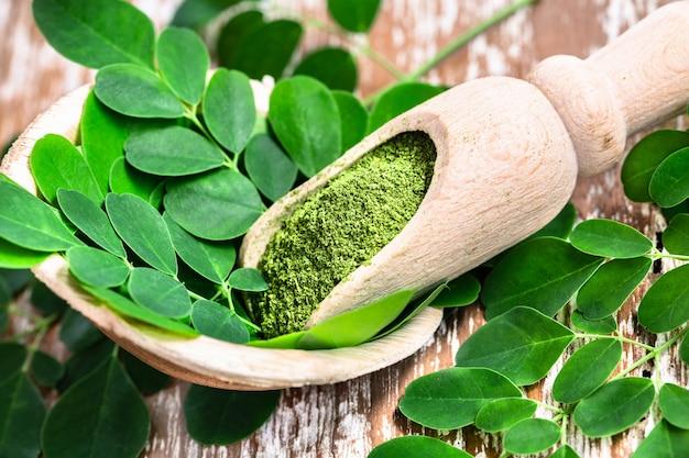 Moringa powder in wooden scoop with original fresh moringa leaves on wooden table. Premium Photo