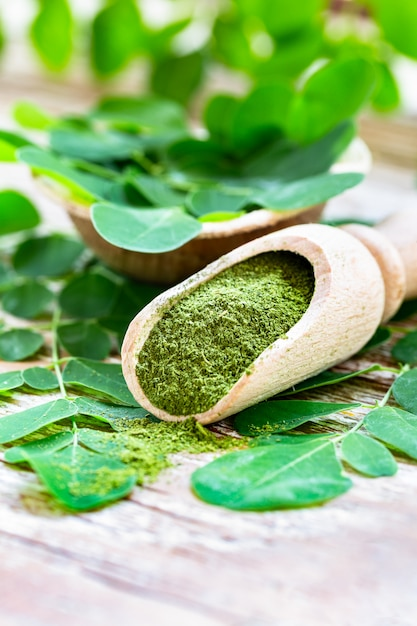 Moringa powder in wooden scoop with original fresh moringa leaves Premium Photo