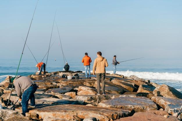 ポルトガルの海の朝。認識できない成人男性の釣りのグループ。釣り竿を持つ未知の漁師。釣り道具。岩の桟橋。 Premium写真