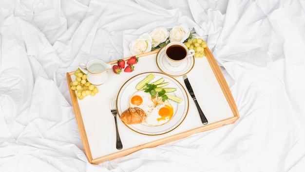 Morning breakfast tray on crumpled bed sheet Free Photo