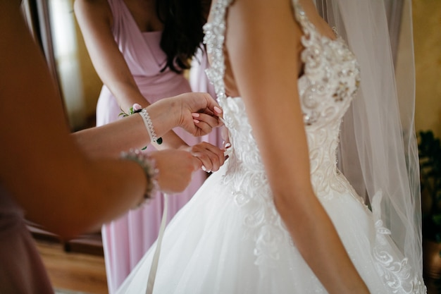 Morning of the bride when she wears a beautiful dress Free Photo