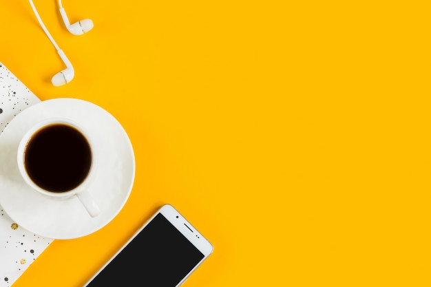 Morning coffee, notebook, mobile phone, plants on a yellow background. business yellow background. Premium Photo