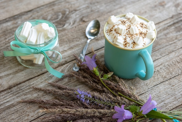 泡とマシュマロとテーブルの上に花と朝のコーヒー。 Premium写真