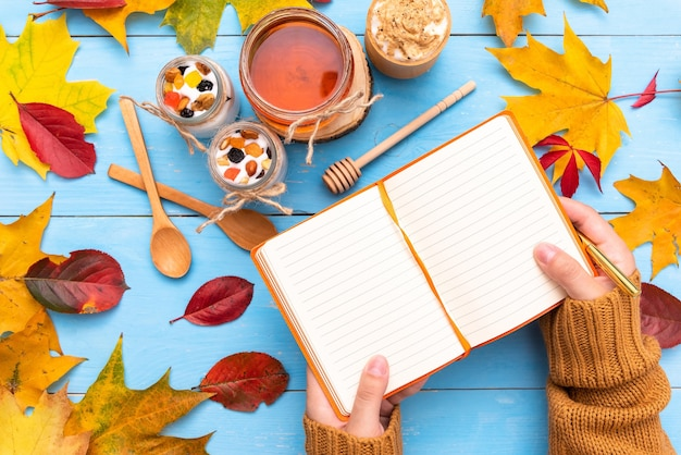 Morning coffee with yogurt and a notepad with autumn leaves. Premium Photo