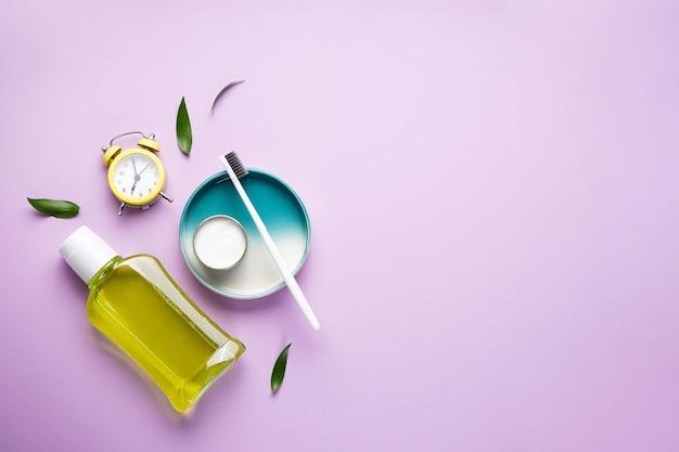 朝のコンセプト、目覚まし時計、紫の歯ブラシのクローズアップ Premium写真