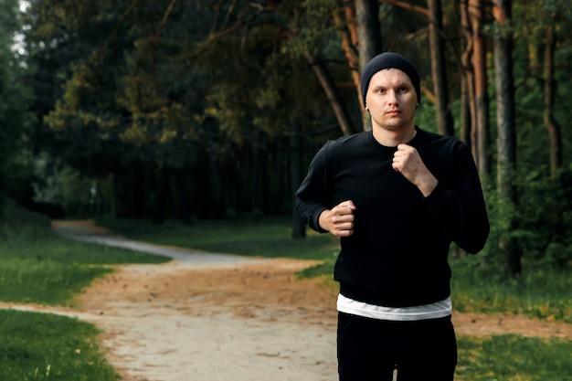 公園での朝のジョギング、公園のコピースペースを走り回っている黒いスポーツスーツの男 Premium写真